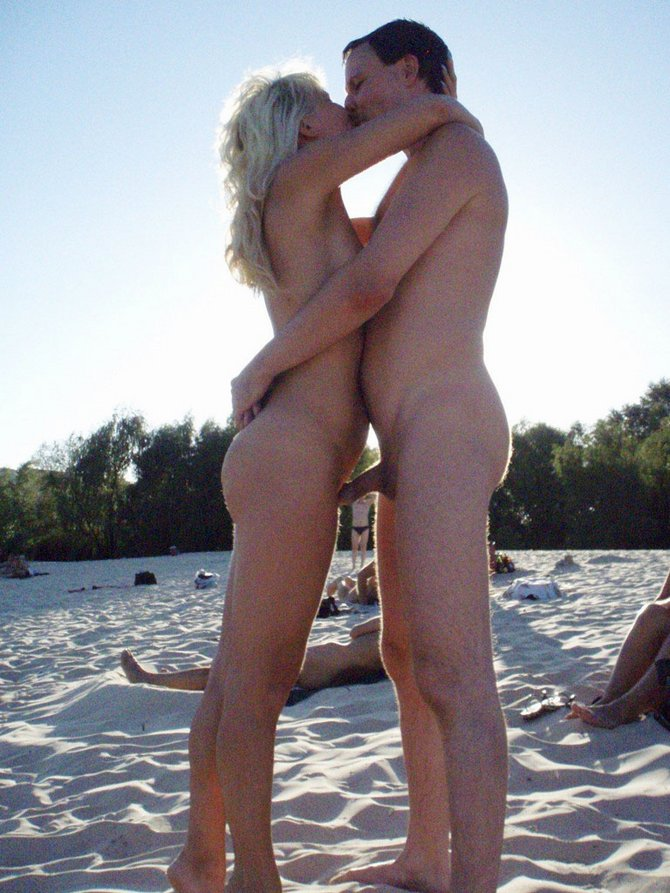 Nude couple kissing on beach